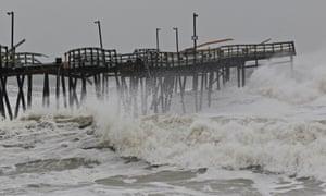 Waves from Hurricane Sandy crash onto the damaged Avalon Pier in Kill Devil Hills,  North Carolina.