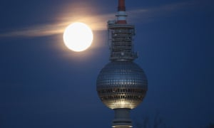 A full moon is visible on a clear evening over the broadcast tower at Alexanderplatz in Berlin, Germany.