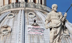 """On top of St. Peter's 130-meter-high dome, at the Vatican. Firefighters look at Italian businessman Marcello di Finizio standing above his banner  which reads """"Help!! Enough Monti, enough Europe, enough multinationals, you are killing all of us. Development?? This is a social butchery!!""""."""