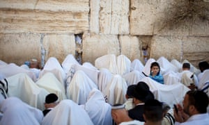 Ultra-Orthodox Jews cover their heads with their prayer shawls and turn away from the Western Wall, Judaism's holiest site, as they recite the Birkat Cohanim or Priestly Blessing in Jerusalem, Israel.