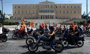 Municipal worker drive their motorcycles during a protest against the new austerity measures outside the Parliament in Athens, on Wednesday, Oct. 3, 2012.