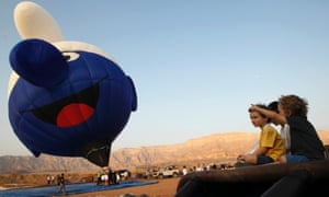 Children watch as a Smurf hot air balloon is prepared for flight during a hot air balloon festival at Timna Park near the southern Israeli city of Eilat.