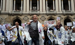 Employees of French drugmaker Sanofi demonstrate against job cuts in Paris.