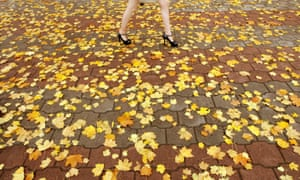 A woman walks on a pavement covered with autumn leaves in central Minsk.