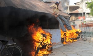 An Indian pedestrian slides down the roof of a police station amid burning motorbikes in Ahmedabad