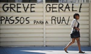 """A woman walks by a graffiti reading """"General Strike! Passos Out!"""" in Lisbon on October 3, 2012."""