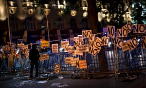 A demonstrator stands next to a fence protecting the Parliament following a demonstration in Madrid, Spain, Saturday, Oct. 27, 2012.
