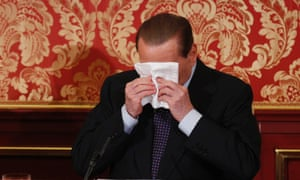 Former Italian Premier Silvio Berlusconi wipes his face during a press conference in Gerno, near Milan, Saturday, Oct. 27, 2012