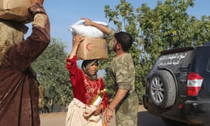 Residents receive humanitarian aid from the Free Syrian Army in Haram town, Idlib province on Monday.