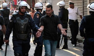 Bahraini riot police detain a man during a protest march in Manama last week