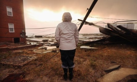 Kim Johnson inspects the area around her apartment building, flooded by Hurricane Sandy. The storm also destroyed large sections of an old boardwalk nearby, in Atlantic City, New Jersey. Johnson fled the area when the water began to rise yesterday.