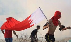 A masked pro-reform protester holds the Bahraini flag