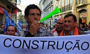 """Retrenched construction workers with a banner reading: """"construction"""" stage a protest demanding to have their jobs back, in front of the economy ministry in Lisbon October 30, 2012."""