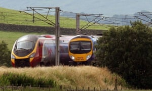 A Virgin train passing a First Group train on the west coast mainline. Photograph: David Cheskin/PA