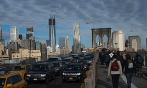 Walking and driving, commuters make their way across the Brooklyn Bridge in New York.