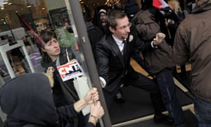 A security guard of a Zara store attemps to stop members of the CGT and CNT worker's unions during a demonstration against the government's cuts in Barcelona on October 31, 2012.