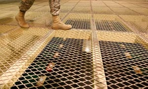 US soldier walks above prison cells at Bagram Air Base