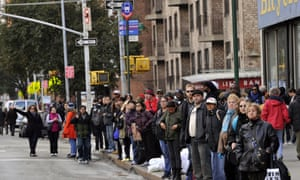 People wait for buses on 6th Avenue in New York amid transit chaos in the aftermath of Sandy.