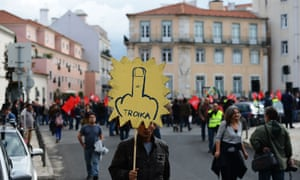 A demonstrator holds a placard during a protest against the Portuguese government's 2013 austerity budget, near the Parliament in Lisbon on October 31, 2012.