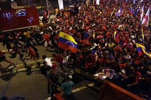 Venezuela elections: Supporters of President Hugo Chavez run towards the Miraflores palace