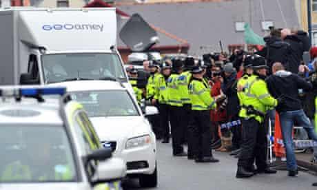 A policeman restrains a man as a van carrying April Jones murder accused Mark Bridger leaves court
