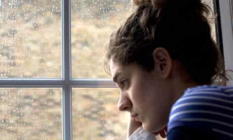 Sad/depressed young woman by rainy window