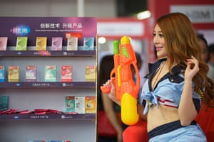 China Sex expo: A model poses with a water pistol on a stand promoting a condom brand