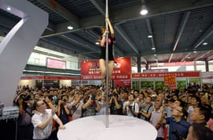 China Sex expo: Spectators photograph a pole dancer on the 007 brand condom stand