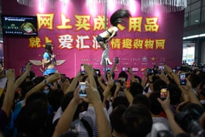 China Sex expo: A pole dancer on a stand promoting a sex products website