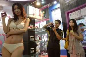 China Sex expo: Visitors photograph a model promoting a personal sex toy