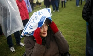 Gladys Plympton, 91, shields herself from the rain prior to Republican presidential candidate Mitt Romney taking the stage for a campaign stop in Newport News, Va.
