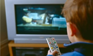 A child holds a remote control while watching television