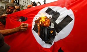 Demonstrators burn a flag emblazoned with a swastika during a demonstration against the visit of German Chancellor Angela Merkel in central Athens, October 9, 2012.