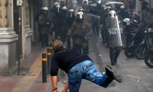 A protester throws a rock at riot policemen in Athens during a demonstration against the visit of Germany's Chancellor Angela Merkel, October 9, 2012.