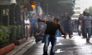 A protester throws a burning cardboard box during a violent protest against the visit of Germany's Chancellor Angela Merkel, in Athens October 9, 2012.