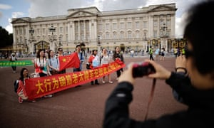 Chinese tourists have their pictures taken outside Buckingham Palace