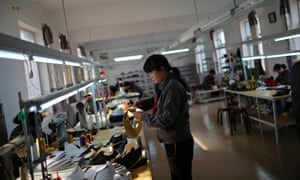 A North Korean worker makes football boots in a temporary factory in the Chinese city of Dandong.