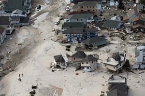 From the agencies: Rescue workers walk past homes wrecked and moved by Superstorm Sandy