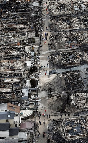 From the agencies: People walk through the remains of burned homes in the Breezy Point, Queens