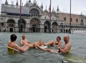 Venice floods: People sit at a table in flooded St Mark's Square