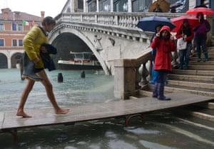 Venice floods: Tourists walk on wooden walkways near the Rialto bridge
