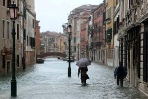 Venice floods: People walk in a flooded street
