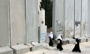 Palestinians going through a wall in Jerusalem
