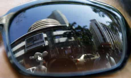 The stock exchange reflected in the sunglasses worn by a pedestrian in Mumbai