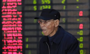 An investor looks at the stock price monitor at a private securities company in Shanghai, China on Tuesday Nov. 13, 2012.