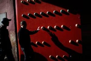Carlos Barria China: A man touches an entrance door of the Forbidden City