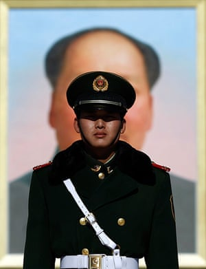 Carlos Barria China: A paramilitary policeman stands guard in front of a portrait of Mao Zedong