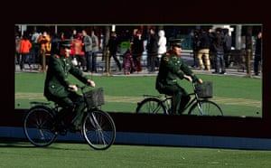 Carlos Barria China: A paramilitary policeman is reflected in a mirror as he rides a bicycle
