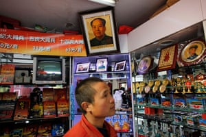 Carlos Barria China: A man walks under a portrait of former Chinese leader Mao Zedong shop