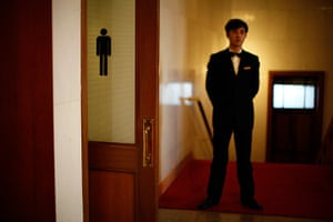 Carlos Barria China: A security officer stands next to the door of a bathroom